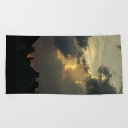 Clouds over  the town Beach Towel