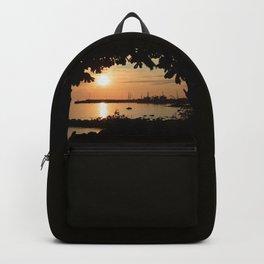Little harbor in golden sunset Backpack