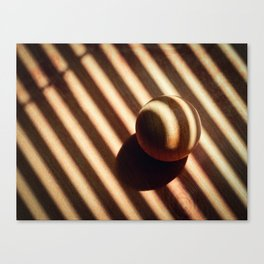 wooden ball covered with the shadow of  sunblinds Canvas Print