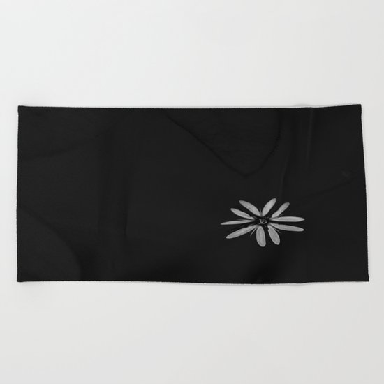 One Tiny White Flower on Black Background Beach Towel