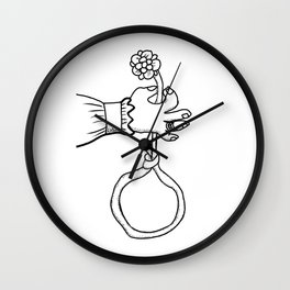 one hand that holds the flower Wall Clock