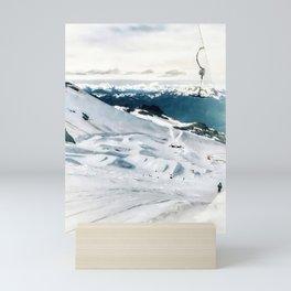 Snowy life on slope under T-bar lifts Mini Art Print