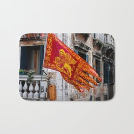 Colors of Venezia, golden-red flag, old building at background Bath Mat
