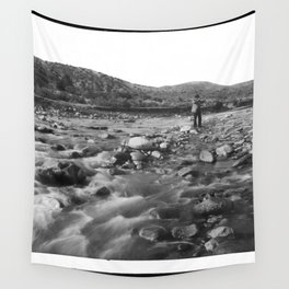 Man with rifle stands in mountain stream as it floods, east of Palmdale, California, ca.1920 Wall Tapestry