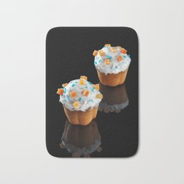 Two small cakes with reflection on a black background. Bath Mat
