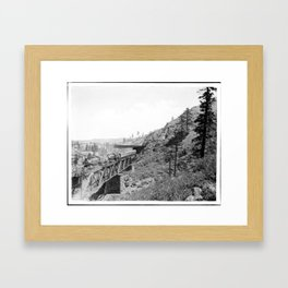 A train of the Southern Pacific Railroad passing over a trestle and into a snow shed in the mountain Framed Art Print
