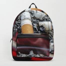 A ruby-colored glass ashtray contained three used cigarette butts along with their ashes A healthcar Backpack