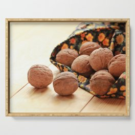 Walnuts scattered from floral pattern bag on sunlit light brown wooden floor Serving Tray