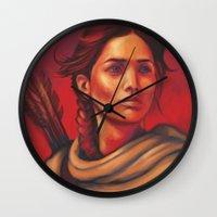 katniss Wall Clocks featuring Katniss by JenHoney