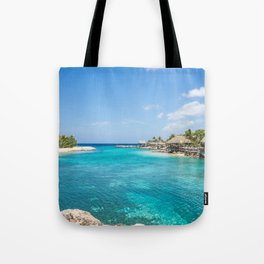 Blue water lake with huts and palm trees around Tote Bag