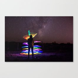 A woman standing at night with lightpainting effects with the lacteal way background Canvas Print