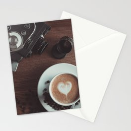 A cup of hot cappuccino placed on a table next to the old camera Stationery Cards