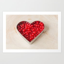 Currants in heart shaped cookie cutter on wood Art Print