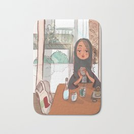 Young Emirati lady enjoying her time in a café Bath Mat