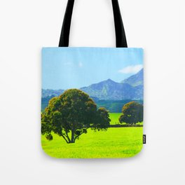 green tree in the green field with green mountain and blue sky background Tote Bag