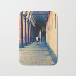 Tourist walking through a hallway with columns in Bologna Italy Bath Mat