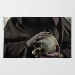 Holding a male skull Rug