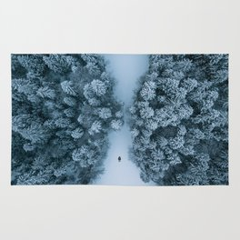 Man lying in the snow on a frozen lake in a winter forest - Landscape Photography Rug
