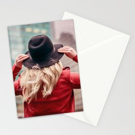A young woman wearing a hat is walking in the streets of New York City Stationery Cards
