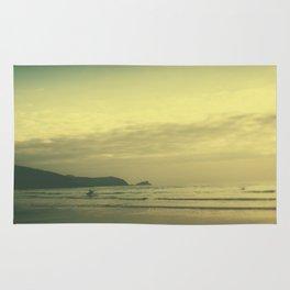 Tilt and shift sun down surfer, Fistral Beach, Newquay, Cornwall Rug