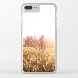 Woman walking through meadow at sunset Clear iPhone Case