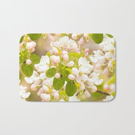 Apple tree branches with lovely flowers and buds on a pastel green background Bath Mat