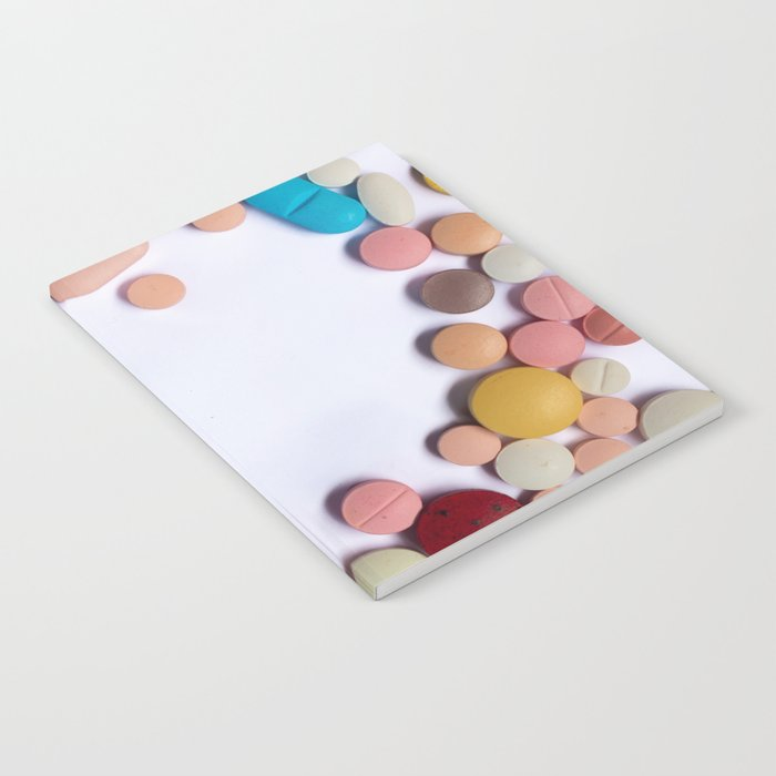 Numerous colorful pills on white background. Notebook