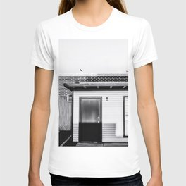 wood building with brick building background in black and white T-shirt