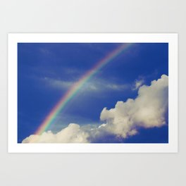Rainbow over fluffy white clouds in the blue sky Art Print