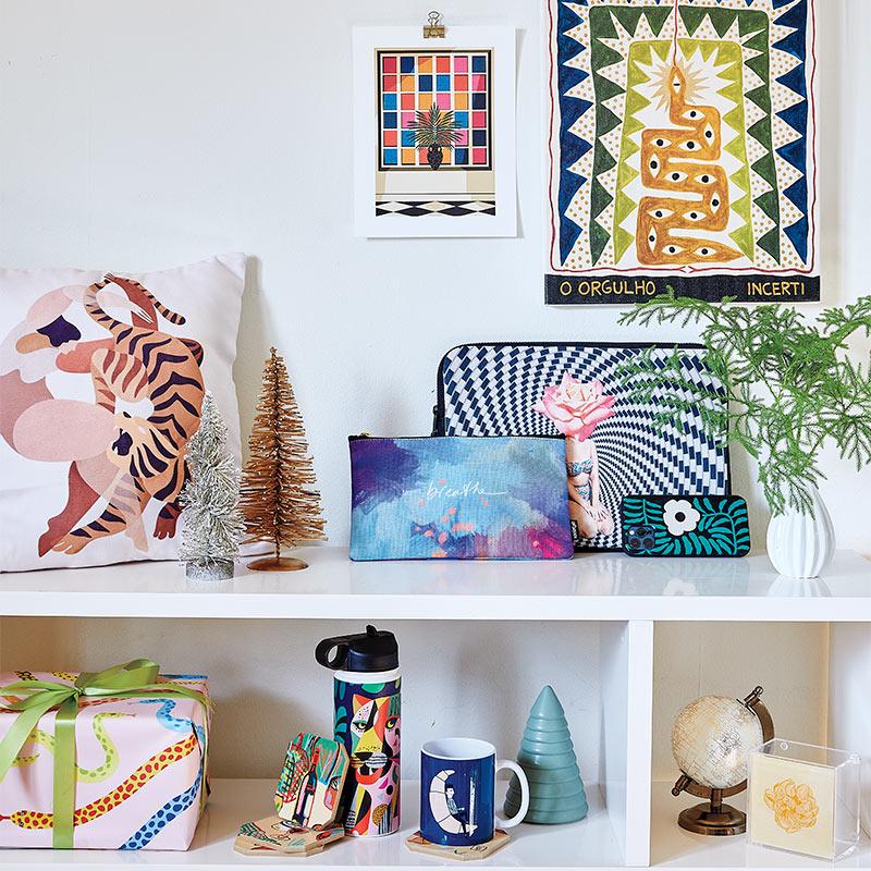 bookshelf showcasing mug, water bottle, throw pillow, laptop sleeve, art prints and more