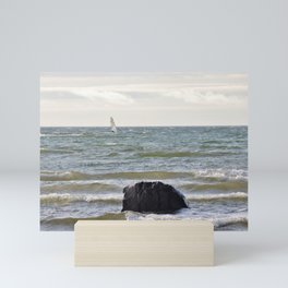 Windsurfer and black stone at gray sea Mini Art Print