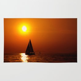 A sailboat at sunset Rug