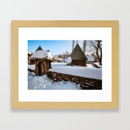 Traditional handcrafted gate and a rural Romanian homestead covered in snow Framed Art Print