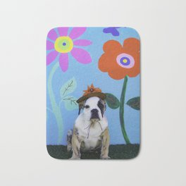 English Bulldog Puppy Wearing a Hat in front of a Spring Background with Tall Flowers Bath Mat