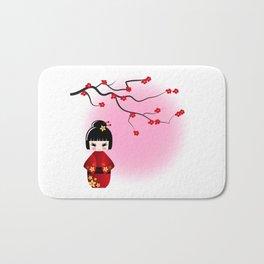 Japanese kokeshi doll at sakura blossoms Bath Mat