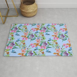 orchids, butterfly and hummingbirds on light blue background Rug