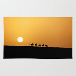 Caravan in the desert during sunset Rug