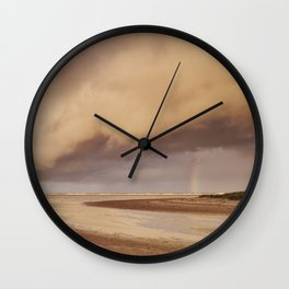 Storm clouds and rainbow at sunset. Holkham, Norfolk, UK. Wall Clock