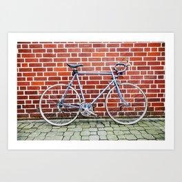 Vintage bicycle against a brick wall Art Print