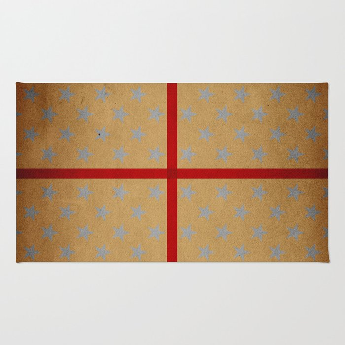 Present wrapped in gold paper and red ribbon Rug