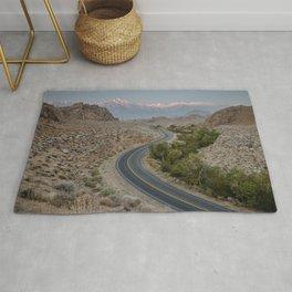GRAY ASPHALT ROAD BETWEEN BROWN MOUNTAINS DURING DAYTIME Rug