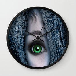 Big green eye in a blue tree Wall Clock