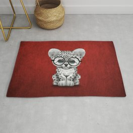 Cute Snow Leopard Cub Wearing Glasses on Deep Red Rug