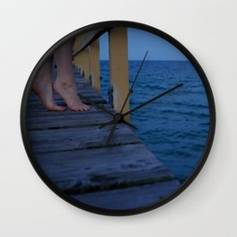 Woman standing on the edge of a pier Wall Clock