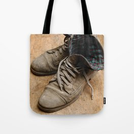 Pair of old leather shoes, worn-out and dusty, on wooden background Tote Bag