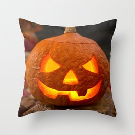 Burning Jack O'Lantern on a rustic table with autumn decorations Throw Pillow