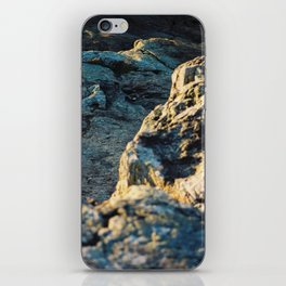 The sun is setting over the rocks iPhone Skin