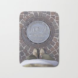 Man standing in front of a manhole Bath Mat