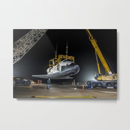 The space shuttle Discovery suspended from a sling held by two cranes Metal Print