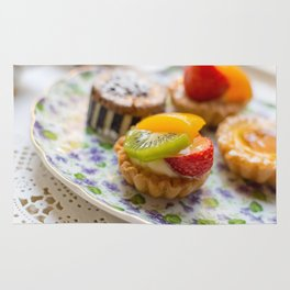 Small fruit tarts laid out on an antique china plate Rug